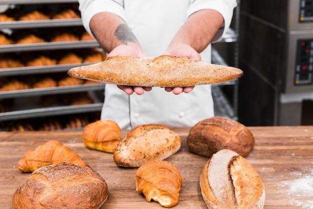 Una mano del panettiere maschio che tiene il pane delle baguette sopra la tavola nella cucina commerciale