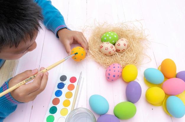 Una mano del ragazzo che dipinge le uova di pasqua. famiglia felice che prepara per pasqua.