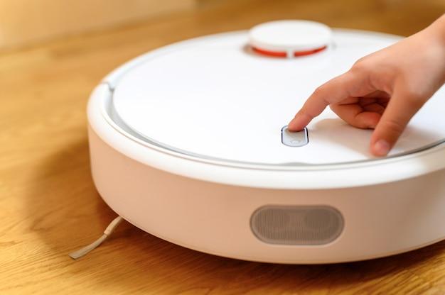 Una mano di bambini preme il pulsante per accendere l'aspirapolvere robot