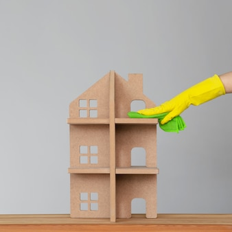 Una mano di donna in un guanto di gomma lava la casa simbolica con un panno verde. il concetto di pulizie di primavera e pulizia.