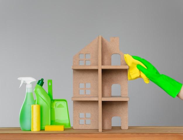 Una mano di donna in un guanto di gomma lava la casa simbolica con un panno verde.
