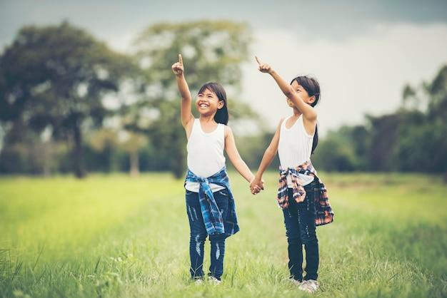 Una mano di due bambine che tiene insieme divertendosi nel parco