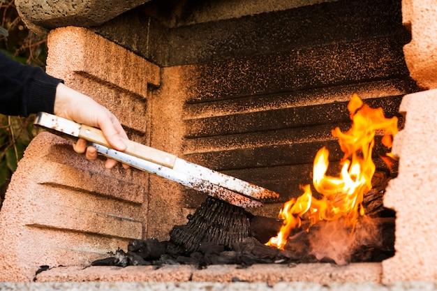 Una mano di persona che brucia carbone con tong in firepit