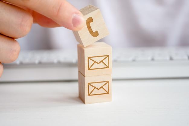 Una mano di uomo detiene un cubo di legno con l'immagine di un simbolo del telefono. i contatti per la comunicazione attraverso la comunicazione, come metodo migliore della corrispondenza.