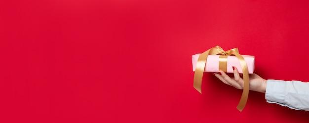 Una mano femminile con una camicia blu da ufficio contiene una confezione regalo a sorpresa con un fiocco rosso