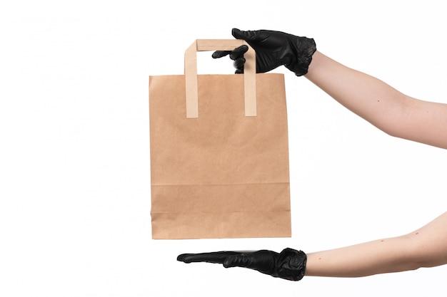 Una mano femminile di vista frontale che indossa i guanti neri che tengono pacchetto di carta su bianco
