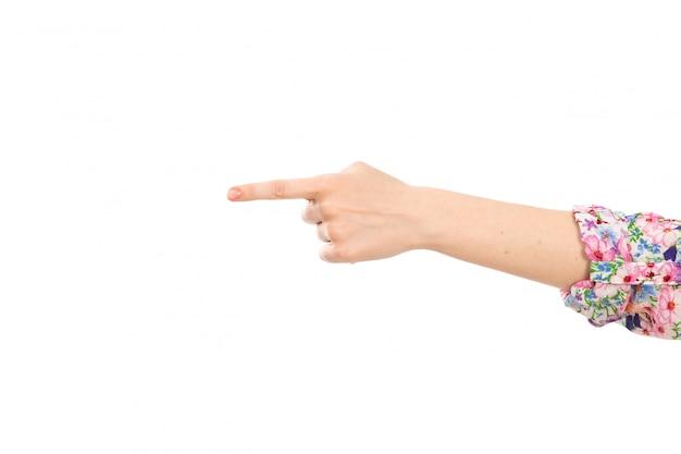 Una mano femminile di vista frontale che mostra il dito che indica il segno sul bianco