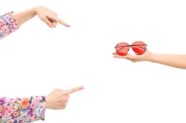 Una mano femminile di vista frontale che tiene gli occhiali da sole rossi con l'altra femmina che precisa negli occhiali da sole sul bianco