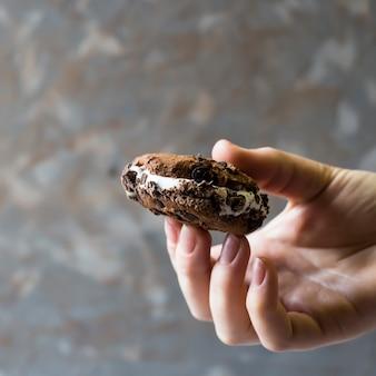 Una mano femminile tiene un panino gelato con un biscotto al cioccolato