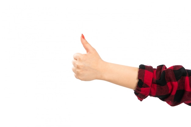 Una mano femminile vista frontale in camicia a scacchi nero-rosso che mostra il segno impressionante sul bianco