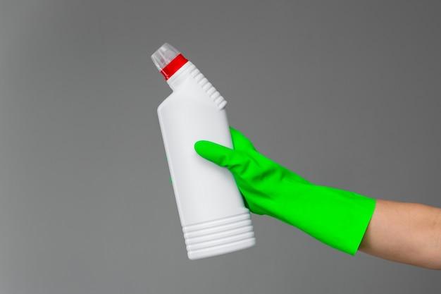 Una mano in un guanto di gomma tiene una bottiglia di detersivo per l'idraulica
