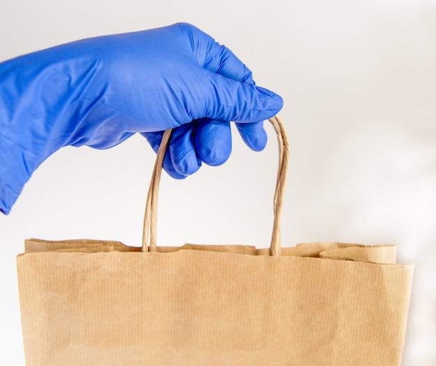 Una mano in un guanto di gomma tiene una shopping bag di carta, consegna cibo in imballaggi ecologici, zero sprechi