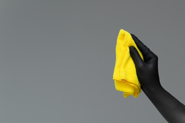 Una mano in un guanto di gomma tiene uno spolverino in microfibra brillante
