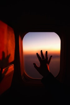 Una mano sopra il finestrino dell'aereo. concetto di viaggio.