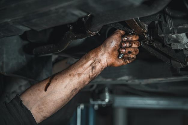 Una mano sporca con una chiave allenta la vite dell'auto durante la riparazione