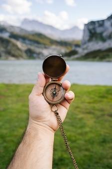 Una mano tiene una bussola in un paesaggio montano e lacustre