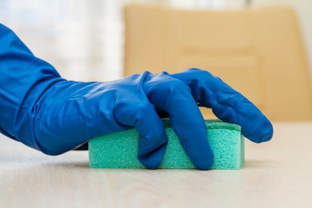 Una mano umana in un guanto protettivo disinfetta il tavolo con una spugna per prevenire i virus