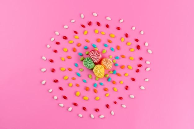 Una marmellata di arance con vista dall'alto e caramelle colorate che formano un cerchio sul colore rosa, zucchero dolce