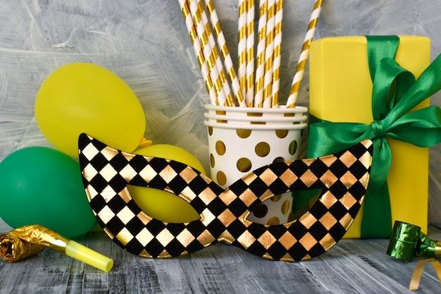 Una maschera nera e oro e vari accessori per le feste