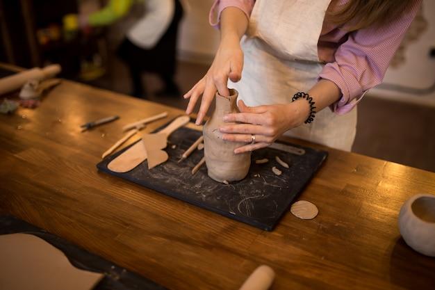 Una master class nel modellare una brocca di argilla. la ragazza è impegnata nella modellistica.