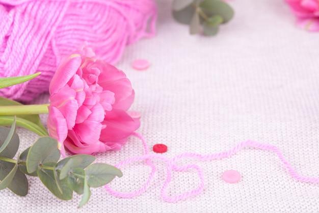 Una matassa del primo piano del filato rosa, bottoni, tulipano. composizione primaverile, tenerezza, cartolina