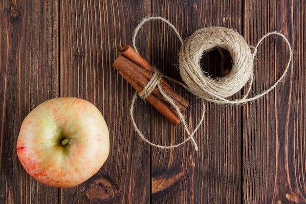 Una mela con cannella secca e corda vista dall'alto su uno sfondo di legno