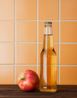 Una mela con la sua vista laterale del succo su uno spazio del fondo delle mattonelle di legno ed arancio per testo