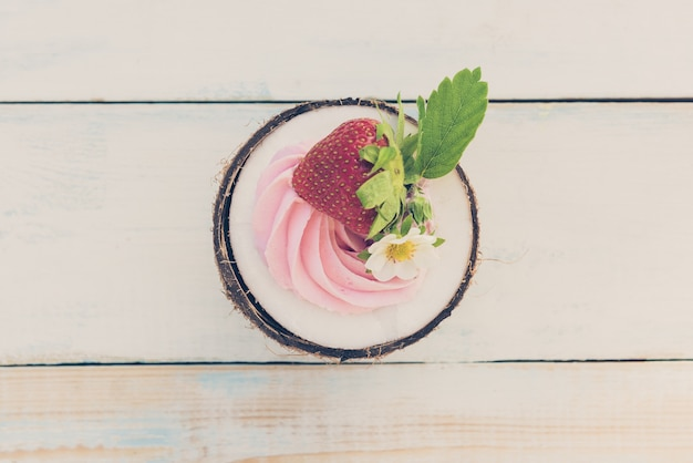 Una mezza noce di cocco rotonda con fragole e crema di formaggio su un tavolo di legno. concetto di salute alimentare. immagine tonica, vista dall'alto