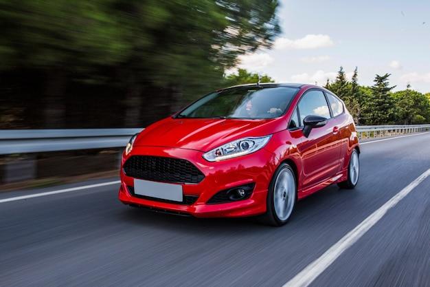 Una mini coupé rossa che guida in autostrada.