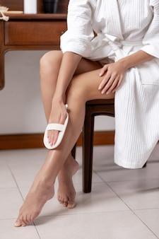 Una modella posa seduta in camice bianco al tavolo della toeletta e si pulisce le gambe con un pennello. cura della pelle del piede.