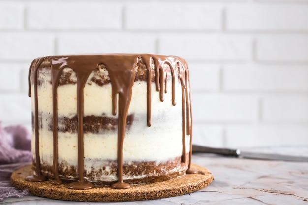 Una moderna torta nuda rotonda con torte marroni e crema di cagliata bianca