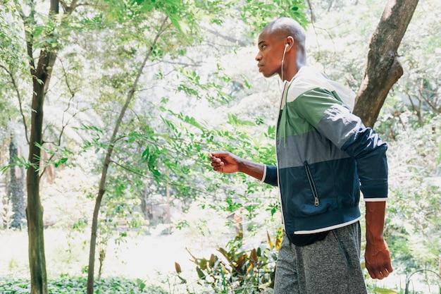 Una musica d'ascolto dell'atleta maschio africano sul trasduttore auricolare che funziona nel parco
