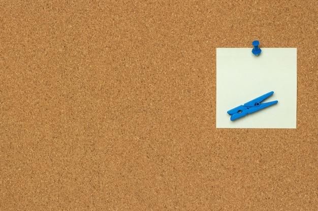 Una nota colorata con puntine da disegno blu e mollette isolati su uno sfondo di sughero