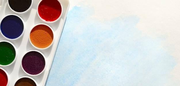 Una nuova serie di acquerelli giace su un foglio di carta, che mostra un disegno ad acquerello astratto sotto forma di tratti blu