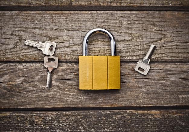 Una nuova serratura con chiavi su un tavolo di legno. il concetto di protezione della proprietà. vista dall'alto.