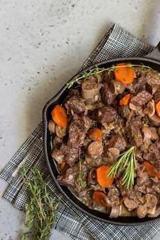 Una padella con bourguignon di manzo con salsicce, carote, aglio, cipolla, vino rosso, erbe e spezie.