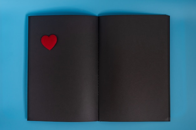 Una pagina vuota del taccuino di carta nera che si trova sulla priorità bassa blu, taccuino aperto