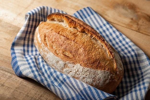 Una pagnotta di pane fresco su un tavolo di legno. vista dall'alto con lo spazio della copia.