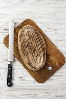 Una pagnotta di pane su un tagliere con coltello