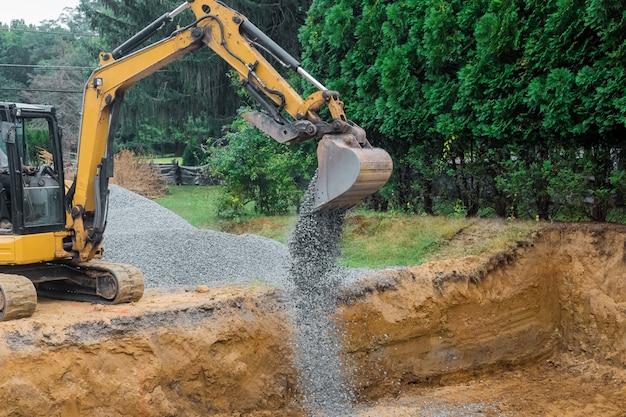 Una pala gialla della benna dell'escavatore che muove la ghiaia delle pietre del fondamento su un cantiere