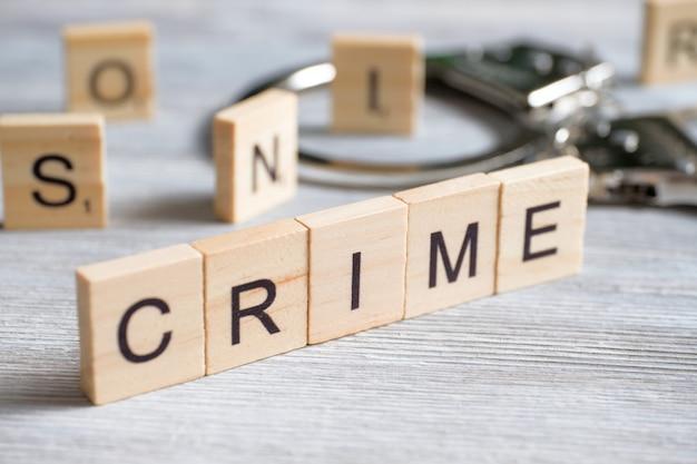 Una parola fatta di lettere di legno è un crimine. manette di metallo su un grigio. il di infrangere la legge.
