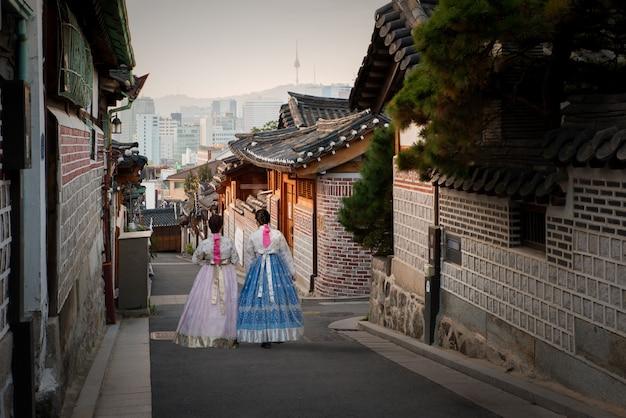 Una parte posteriore di due donne che indossano hanbok che cammina nel villaggio di bukchon hanok a seoul, corea del sud.