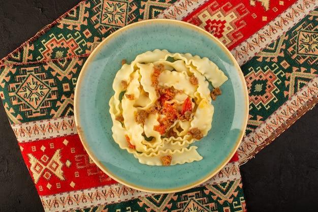 Una pasta con vista dall'alto cucinata gustosa salata all'interno di un piatto verde rotondo su un tappeto progettato e una scrivania scura