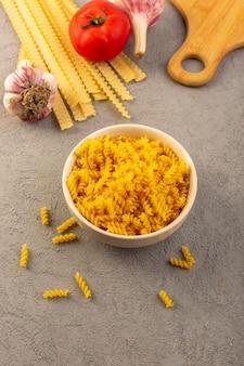 Una pasta cruda asciutta lunga gialla gialla della pasta cruda di vista superiore con aglio e pomodori rossi e forcella isolati sul pasto grigio dell'alimento delle verdure del fondo