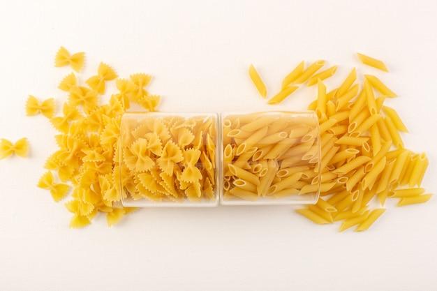 Una pasta cruda asciutta pasta gialla italiana di vista superiore dentro le ciotole di plastica trasparenti e diffusione sul pasto bianco dell'alimento del fondo bianco