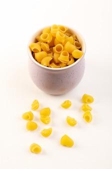 Una pasta gialla cruda della pasta asciutta italiana di vista frontale dentro la ciotola sul bianco