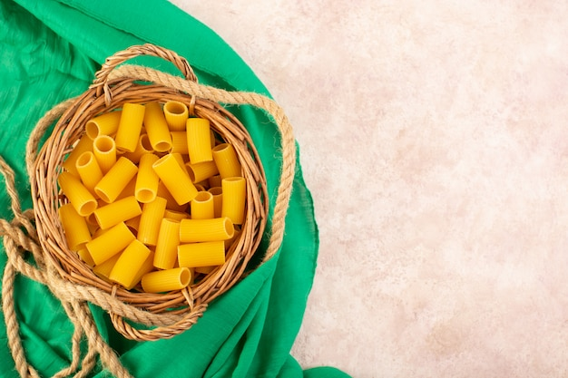 Una pasta italiana cruda di vista superiore gialla all'interno del piccolo canestro con le corde sul tessuto verde e sul rosa