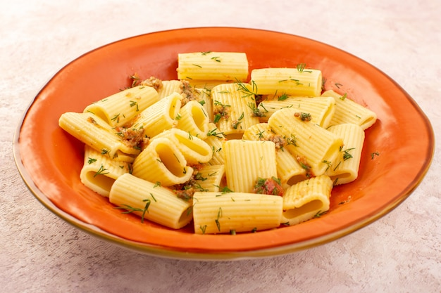 Una pasta italiana di vista frontale chiusa cucinata gustosa con verdure secche e salata all'interno del piatto arancione rotondo sullo scrittorio rosa
