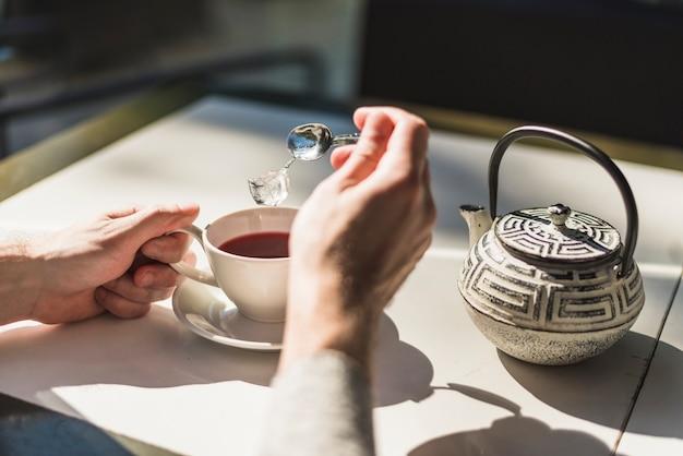 Una persona che aggiunge il cubetto di ghiaccio nella tazza di tè rossa