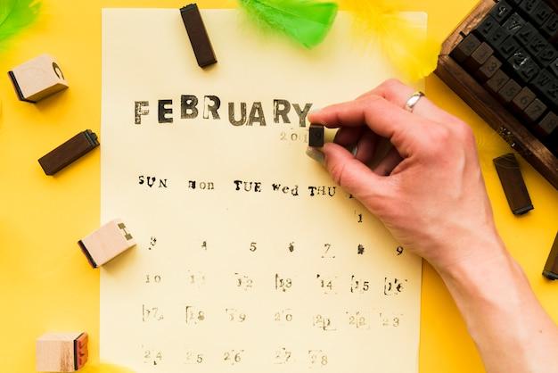 Una persona che fa il calendario di febbraio con blocchi tipografici su sfondo giallo
